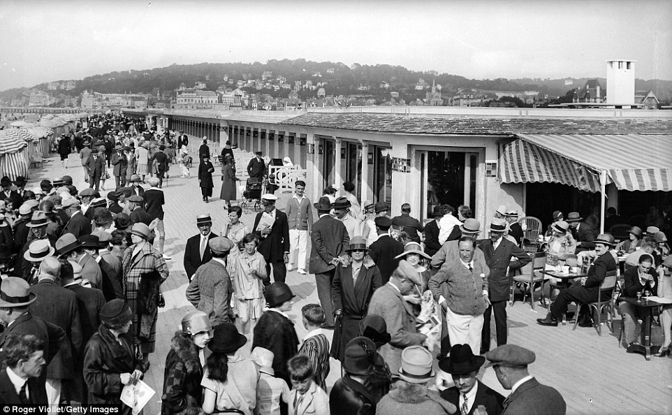 Slide 9 of 25: Another shot of Deauville in 1920 shows the boardwalk packed with holidaymakers wearing formal attire on their day out.