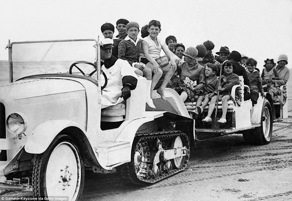 Slide 13 of 25: By 1925, Deauville was doing a roaring trade in tourism. Above, families sit on the tour bus that takes them along the beach.