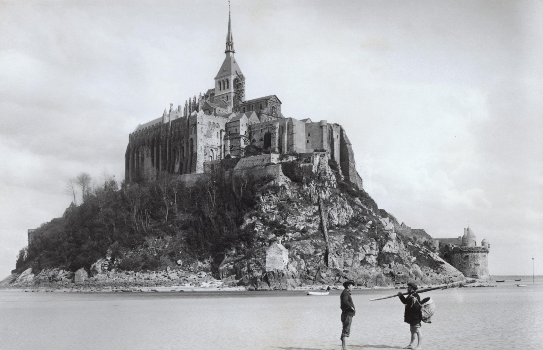 Slide 16 of 51: A picturesque monastery sitting atop a small island off the coast of Normandy, Mont Saint-Michel is one of the most visited landmarks in France. Built in the 8th century, it was a popular attraction from the get-go, drawing in a vast number of pilgrims from across Europe who were desperate to see the magnificent structure. Pictured here in circa 1900, two fishermen can be seen on the tidal flats in the foreground.