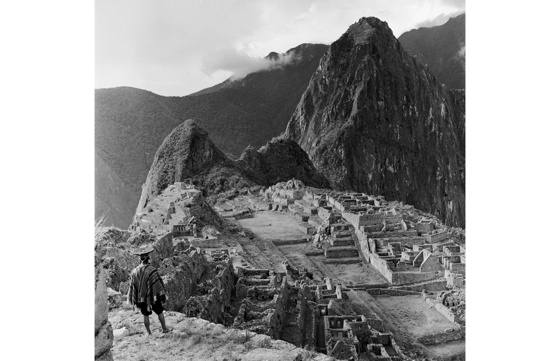 Slide 38 of 51: A well-preserved citadel dating back to the Inca Empire which ruled over western South America in the 15th and 16th centuries, Machu Picchu is located around 50 miles (80km) northwest of Cuzco, between the peaks of its namesakeand Huayna Picchu. It became well-known to the Western world when American archaeologist Hiram Bingham and his team began digging there in 1911, after which Bingham published a book, The Lost City of the Incas, which led tourists to flock to the Inca Trail. Pictured here in the mid-1950s, a Peruvian Indian man in traditional dress gazes out at the view.