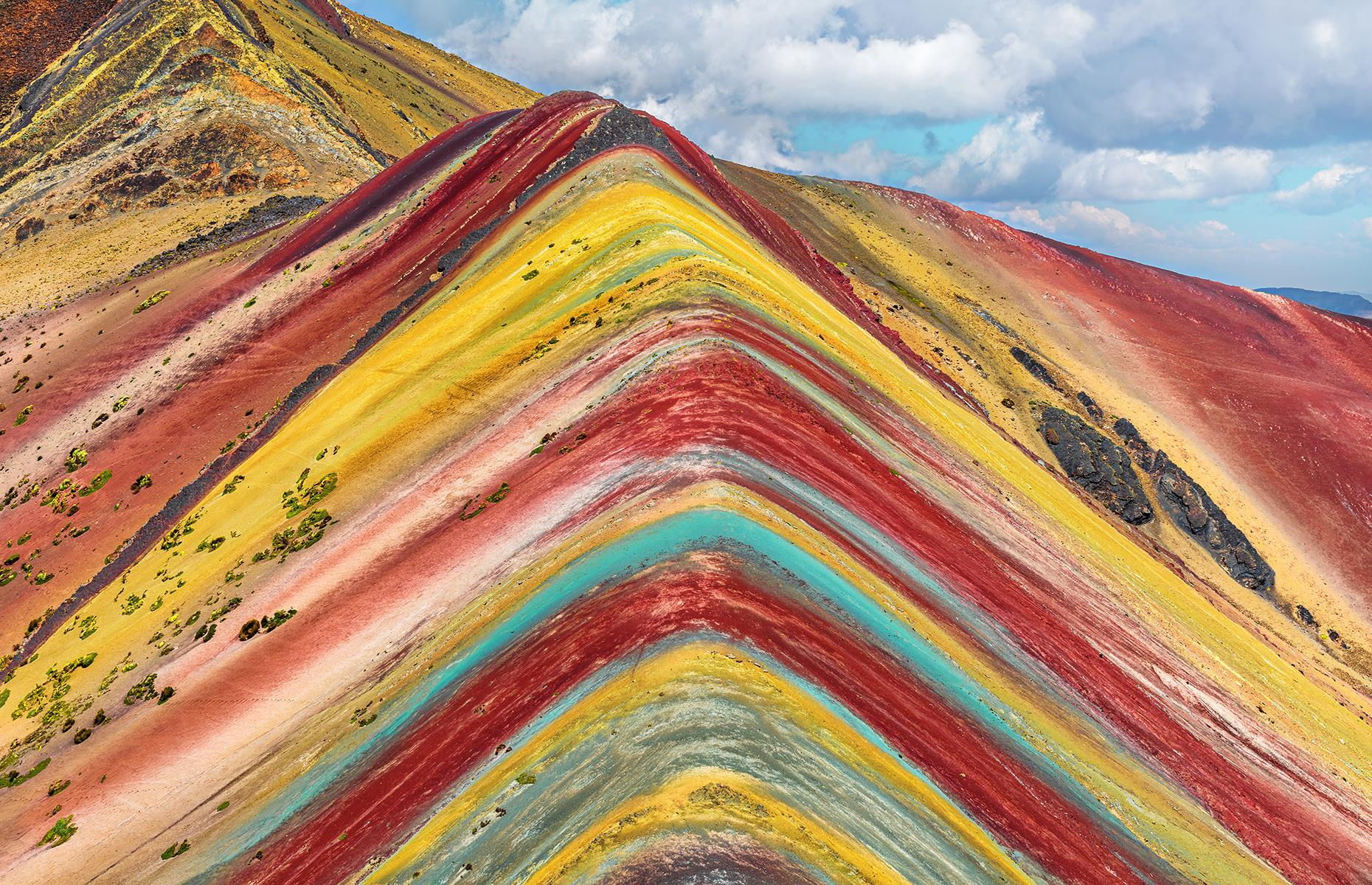 Slide 6 of 41: This multicolored mountain in the Peruvian Andes is not man-made despite what its perfectly symmetrical layers might make you think. The colorful bands, ranging from pink and red to yellow and green, are the result of sedimentary layers forming from mineral deposits over the years.