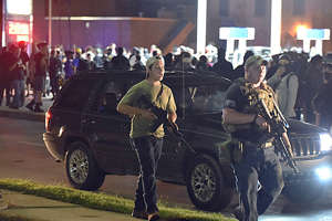 a group of people standing in front of a car: Kyle Rittenhouse, left, walks along Sheridan Road in Kenosha, Wis., on Aug. 25 with another armed civilian. Prosecutors charged Rittenhouse, 17, from Illinois, in the fatal shooting of two protesters and the wounding of a third during a night of unrest after the police shooting of Jacob Blake.
