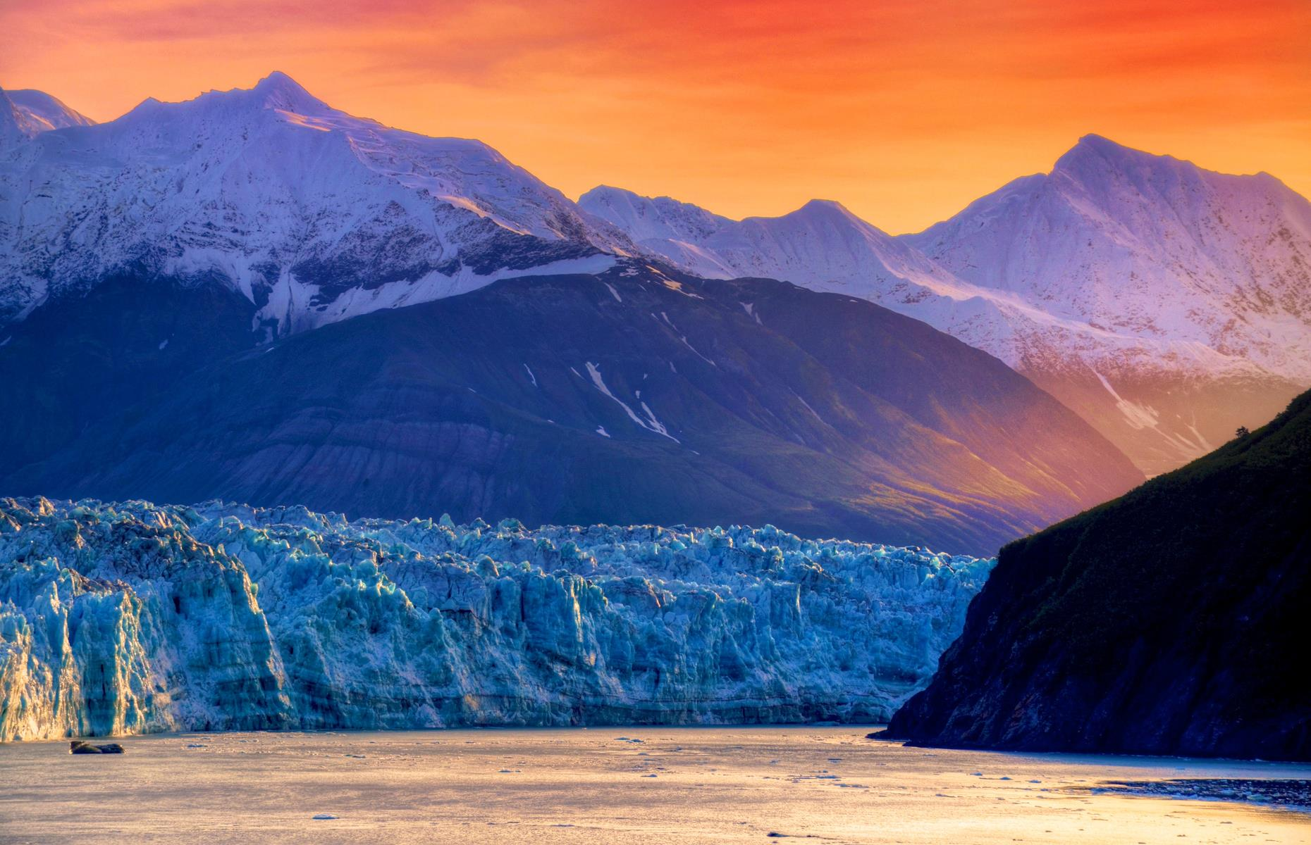 Slide 3 of 51: The gigantic Hubbard Glacier in Wrangell-St. Elias National Park is more than seven-miles (11km) wide, 76-miles (122km) long and reaches a height of 600 feet (183m). So it's breathtaking at any time of day. At the break of dawn, however, a backdrop of blazing tangerine makes it even more majestic. The thunderous roar of ice chunks calving from the glacier and plunging into the frigid waters below adds to the drama.