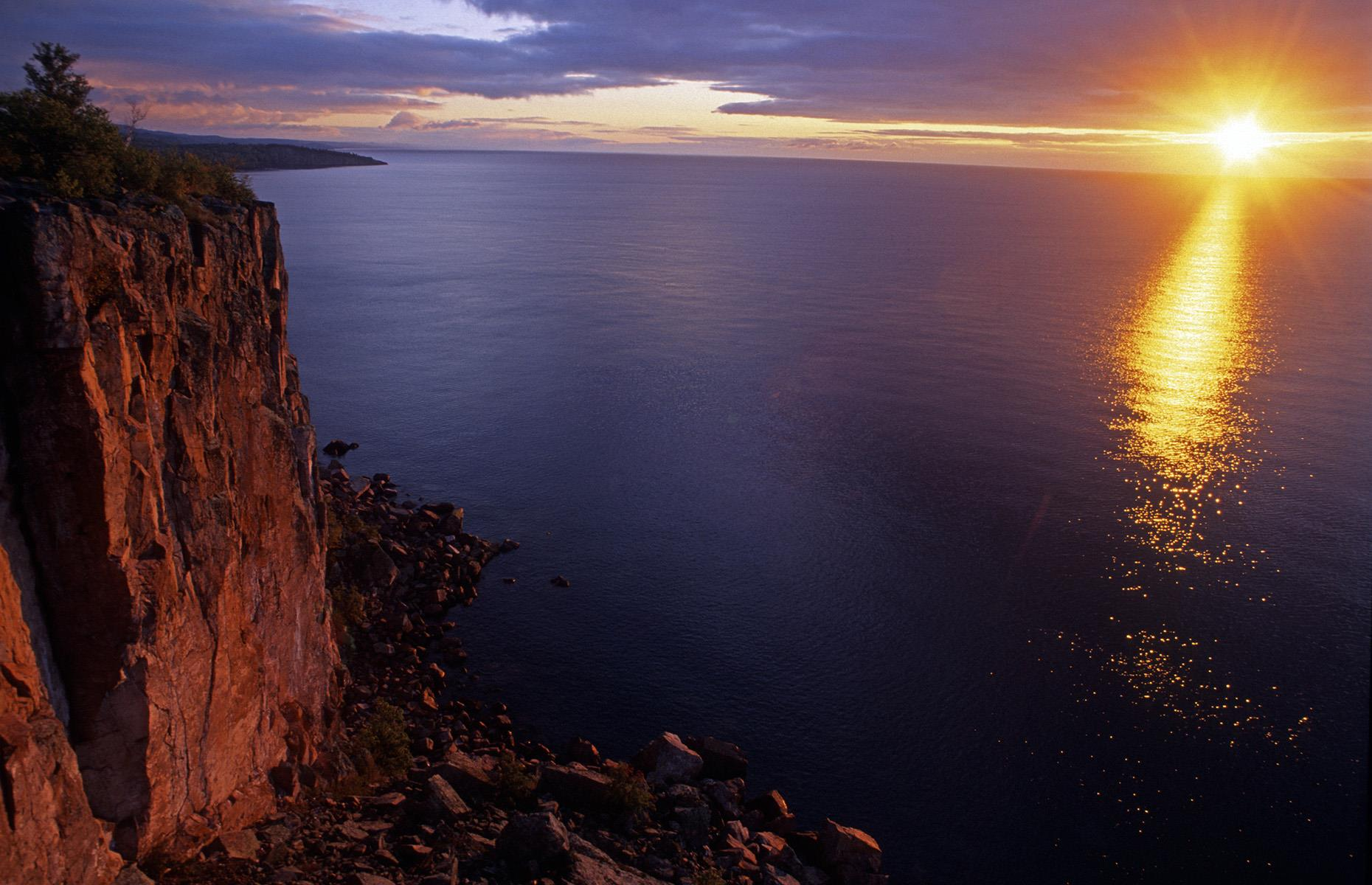 Slide 24 of 51: This huge, sheer-faced rock formation perches dramatically at the edge of Lake Superior's north shores, and sees glorious sunrises day after day. Dawn breaks its way through the skies and sends beams skimming across the lake's silvery surface, creating a bold contrast with the inky waters. Palisade Head is part of Tettegouche State Park, an endlessly inspiring landscape of forests, waterfalls and lakeside cliffs where peregrine falcons nest.