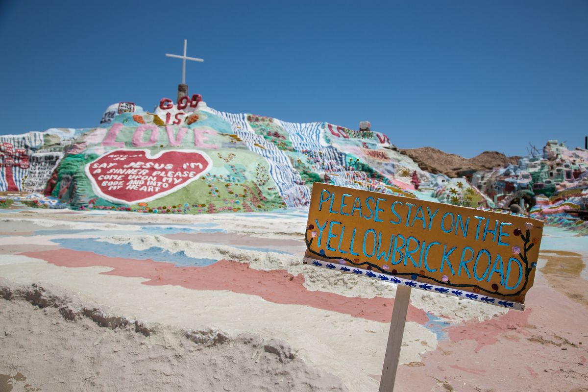 "Slide 16 of 18: This brightly painted mountain in Niland, California, was designed by Leonard Knight as a tribute to God, with the big message ""God Is Love"" at the center. The mountain stands 50 feet tall and 150 feet across and is made of clay and painted with biblical messages."
