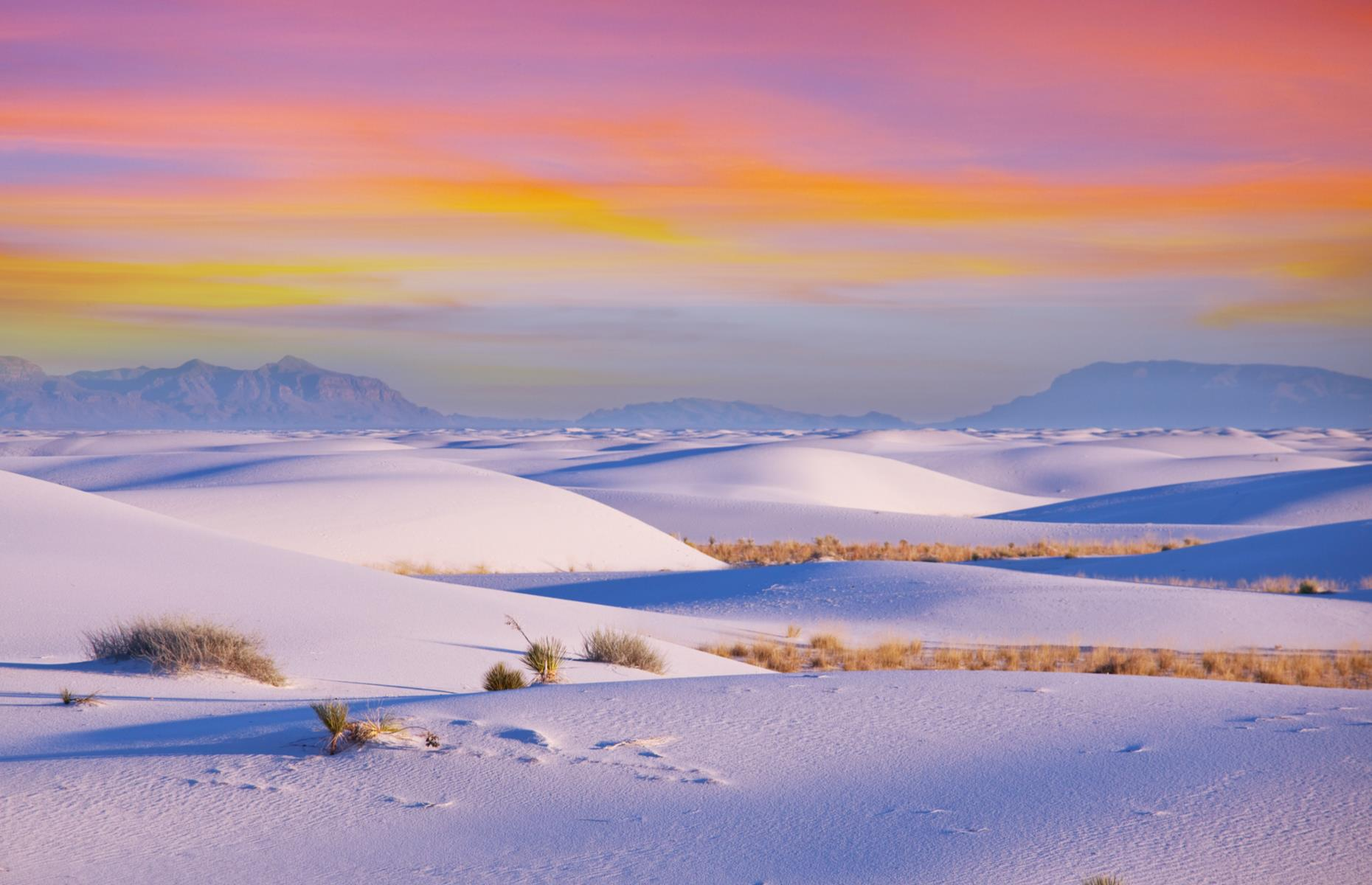 Slide 32 of 51: It's hard to believe a landscape like this exists anywhere on Earth, let alone in New Mexico. At first glance, White Sands National Monument looks like a snowscape, with bright white waves rolling for miles. The dunes look even starker at dawn, when ocher and pink-streaked skies pop against the icing-sugar-colored sand.