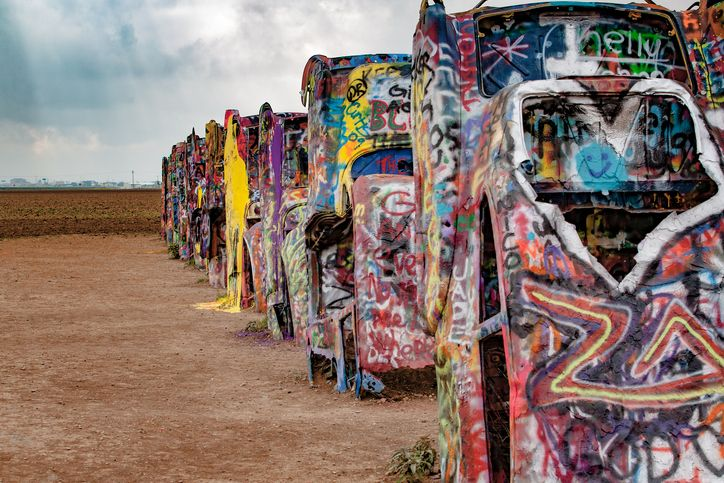 Slide 12 of 18: This iconic art instillation was created in 1974, and features 10 Cadillacs that appear to be growing out of the ground. They've been covered in graffiti by visitors and if you bring your own paint, you are allowed to leave your mark on this free monument.