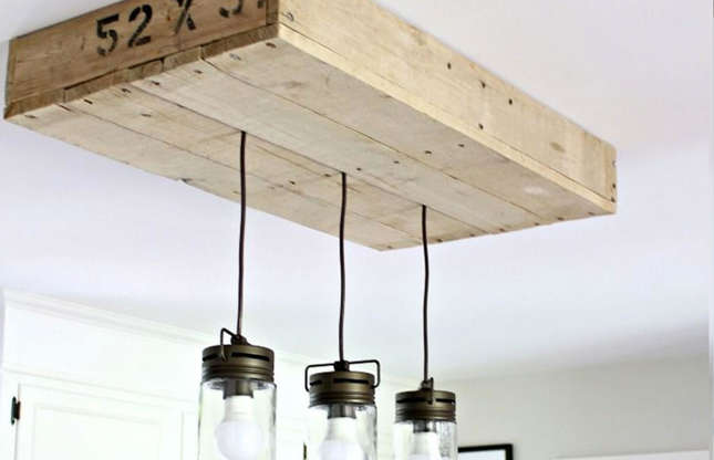 Slide 4 of 56: What an ingenious idea for hiding an ugly light fitting! This pallet lightbox has been made by@NotingGraceforRemodelaholicusing pallet wood scraps from other projects. Thisnot only covers up the electrical ceiling power socket but separates a trio of industrial-styleglass pendant lightsover a kitchen island.