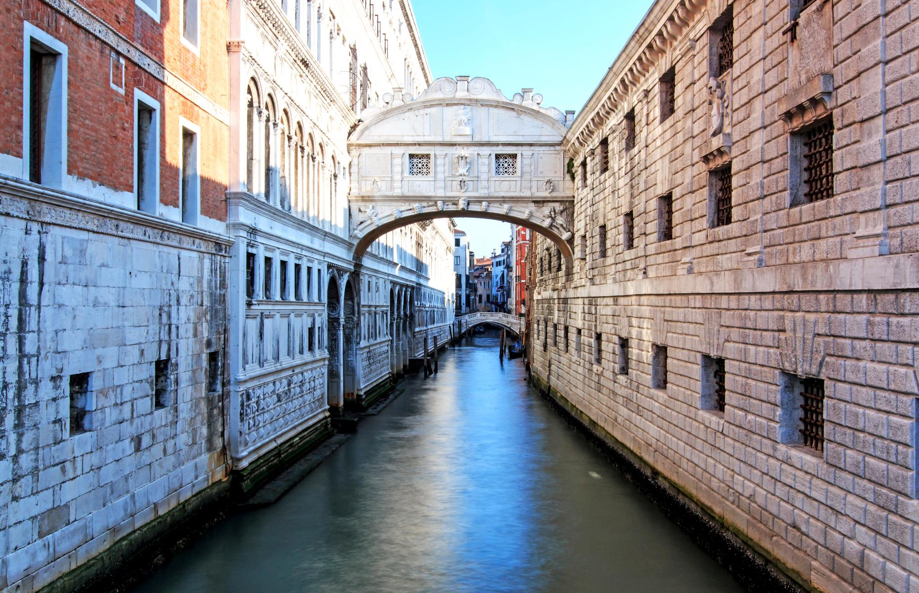 Slide 21 of 31: Often touted as one of the most beautiful bridges in the world, and certainly one of the most photographed, Venice's Ponte dei Sospiri, or Bridge of Sighs, was constructed around 1600. It was built to connect the old prison and interrogation rooms in the Palazzo Ducale to the newer prison across the canal, and its name reportedly comes from the sighs of the prisoners who crossed its expanse. Legend has it that if a couple kisses under the bridge while on a gondola at sunset, they will enjoy eternal love.