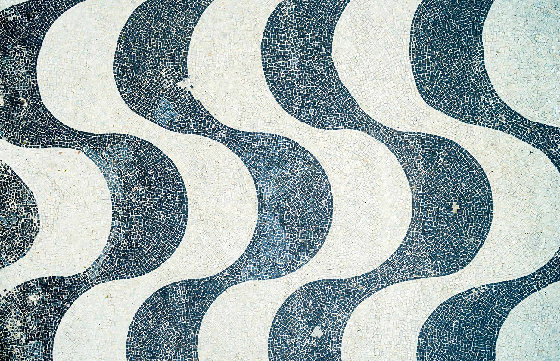 Slide 32 of 53: Located in Brazil's second-largest city, these tiles form a promenade along one of the most famous beaches in the world. Designed by Roberto Burle Marx, the promenade was first built in the 1930s and then restored in 1970.