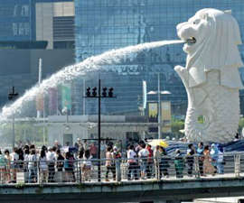 a group of people standing in front of a building: Merlion