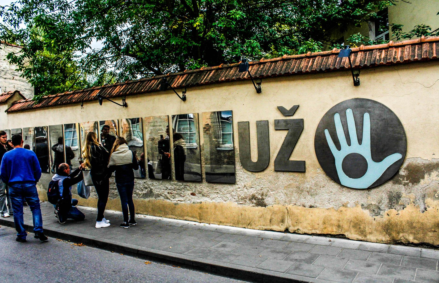 "Slide 19 of 26: The symbol of Užupis is the ""Holy Hand"": a blue hand with a hole in the middle, symbolizing an inability to accept bribes and there's nothing to hide. The micronation's creative community usually regularly hosts fashion festivals, concerts, exhibitions and poetry events."