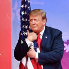 TOPSHOT - US President Donald Trump hugs the US flag as he arrives to speak at the annual Conservative Political Action Conference (CPAC) in National Harbor, Maryland, on March 2, 2019. (Photo by NICHOLAS KAMM / AFP) / ALTERNATIVE CROP (Photo by NICHOLAS KAMM/AFP via Getty Images)