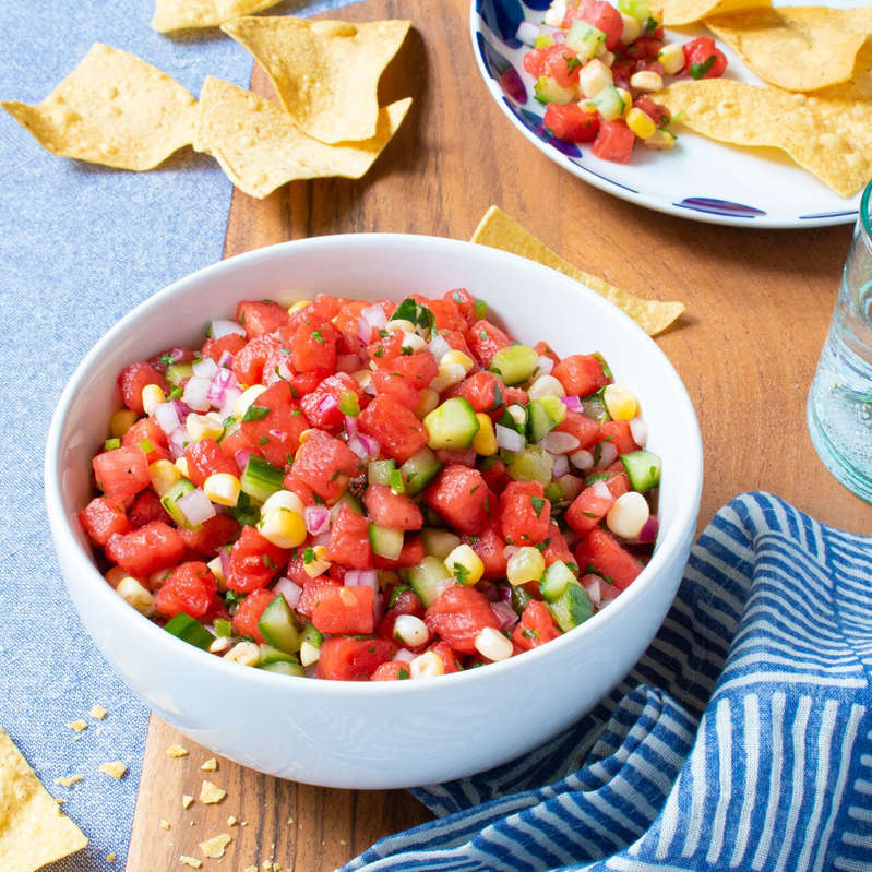 a bowl of food on a plate on a table: Watermelon, Cucumber & Corn Salsa