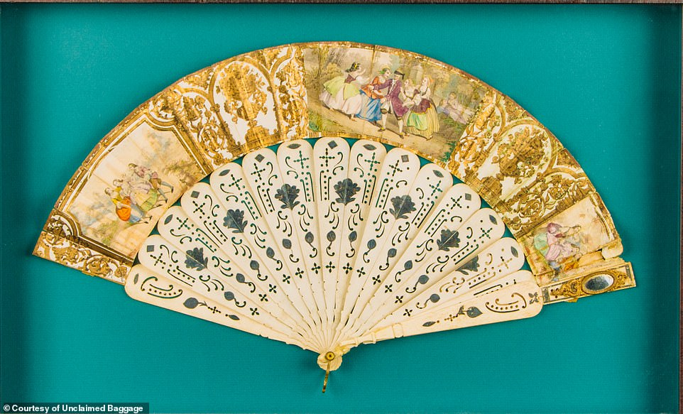 "Slide 6 of 18: 'FLIRTING' FAN FROM THE 1800s: A 'beautiful', hand-painted 'flirting fan' from the Victorian period once turned up at Unclaimed Baggage. Gilded in gold and reinforced with intricately-carved bone, ladies throughout Europe used these fans to subtly communicate with men at social gatherings from the 16th to 19th centuries. The company adds: 'A small ""flirting mirror"" in the fan's top right corner allowed a lady to discreetly see whether her flutters were achieving the desired effect.'"