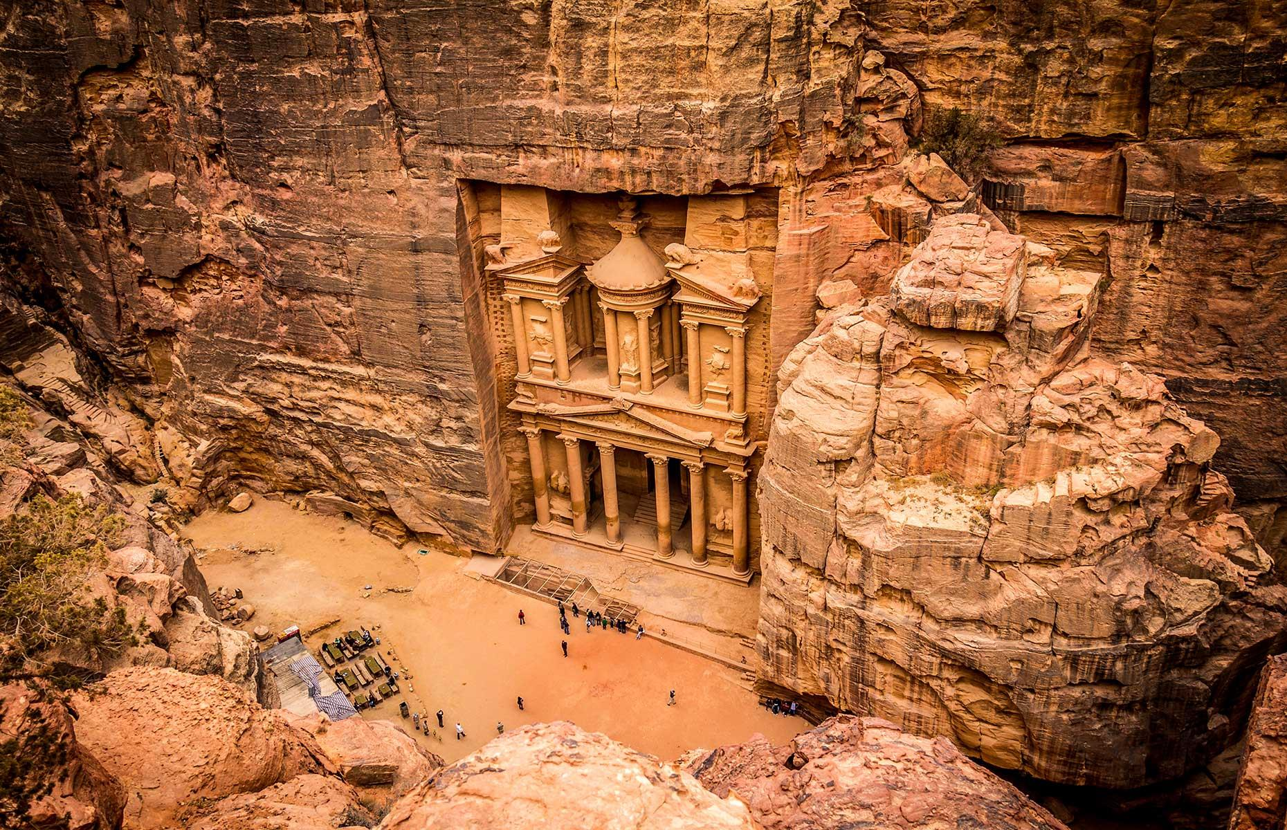 Slide 27 of 30: Known as the Rose City, Petra in southern Jordan was carved into the pink sandstone cliff faces of desert canyons by the Nabataeans in the 1st century BC. The entrance to the city, flanked by 262-foot high (80m) cliffs, opens up onto the Al Khazna or Treasury (pictured). This 131-foot high (40m) building decorated with Corinthian columns and freezes, was probably built in the 1st century BC.