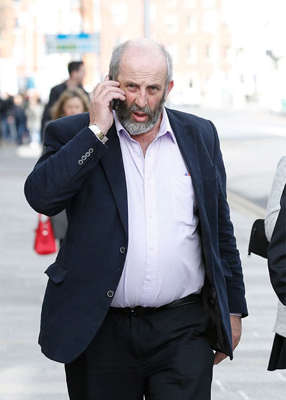 a man wearing a suit and tie talking on a cell phone: The latest COVID-19 numbers come as the Healy-Rae family have said they are 'looking at circumstances' of a video that appears to show people allegedly breaking public health guidelines. Pic: RollingNews.ie