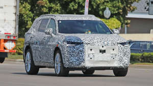 a truck that is driving down the road: Three-row 2022 Buick Envision GX caught in these spy photos.