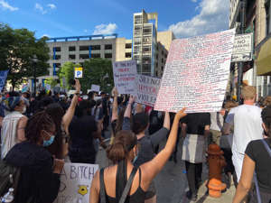 a group of people standing in front of a crowd: Marchers in Baltimore on June 1, during a protest over the killing of George Floyd in Minneapolis police custody.The sign lists the names of African Americans killed.