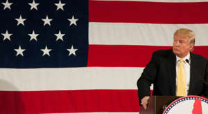 Donald Trump holding a sign: Photo of Donald Trump standing at a podium with the American flag in the background