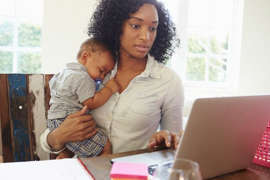 a person sitting at a table using a laptop: A mother holds an infant while she works on her computer.