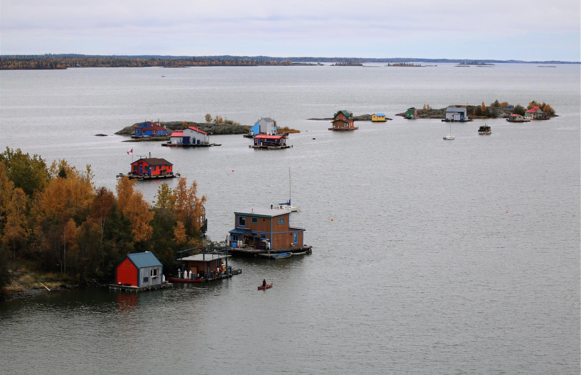 Slide 15 of 31: Yellowknife sits right on Great Slave Lake and the lake is very much part of the city. A community of houseboats floats in Yellowknife Bay during the summer. In wintertime when the lake is frozen over, the boats sit on frozen ice, allowing residents to walk or drive into town.