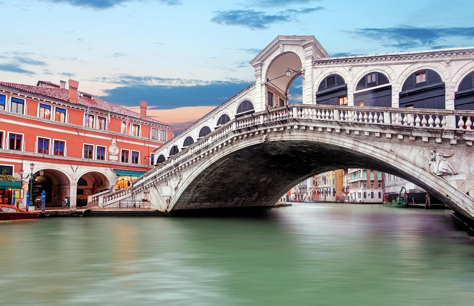 Slide 21 of 31: Another symbol of Venice is the 16th-century Rialto Bridge (pictured) – or Ponte di Rialto – that crosses over the narrowest point of Venice's Grand Canal and is held up as a great feat of Renaissance-era architecture. An elegant arch complete with stone reliefs, the bridge has been damaged and rebuilt several times, but is still the oldest of the four bridges crossing the Grand Canal.