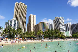 a group of people swimming in the water with a city in the background: File photo of Waikiki Beach.
