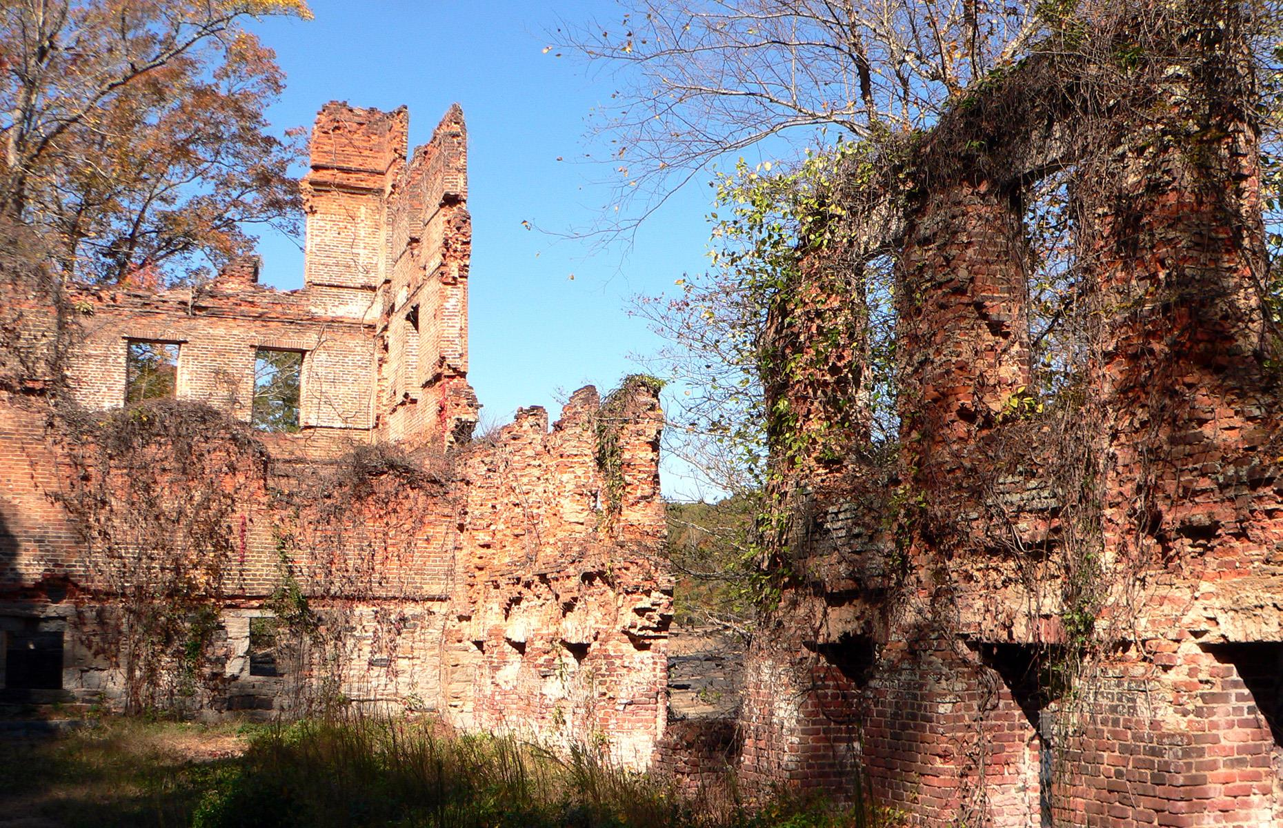 Slide 12 of 52: Today, the crumbling remains of the New Manchester Manufacturing Company are shrouded by the forest of Sweetwater Creek State Park. Dating back to the mid-1800s, the building was originally a working textile mill, but it was almost burned to the ground by Union troops during the Civil War. Trails lead to the red-brick ruin and visitors can even peek inside on a guided hike (currently still running). Sweetwater Creek State Park is open, but access may occasionally be restricted if crowds become too large.