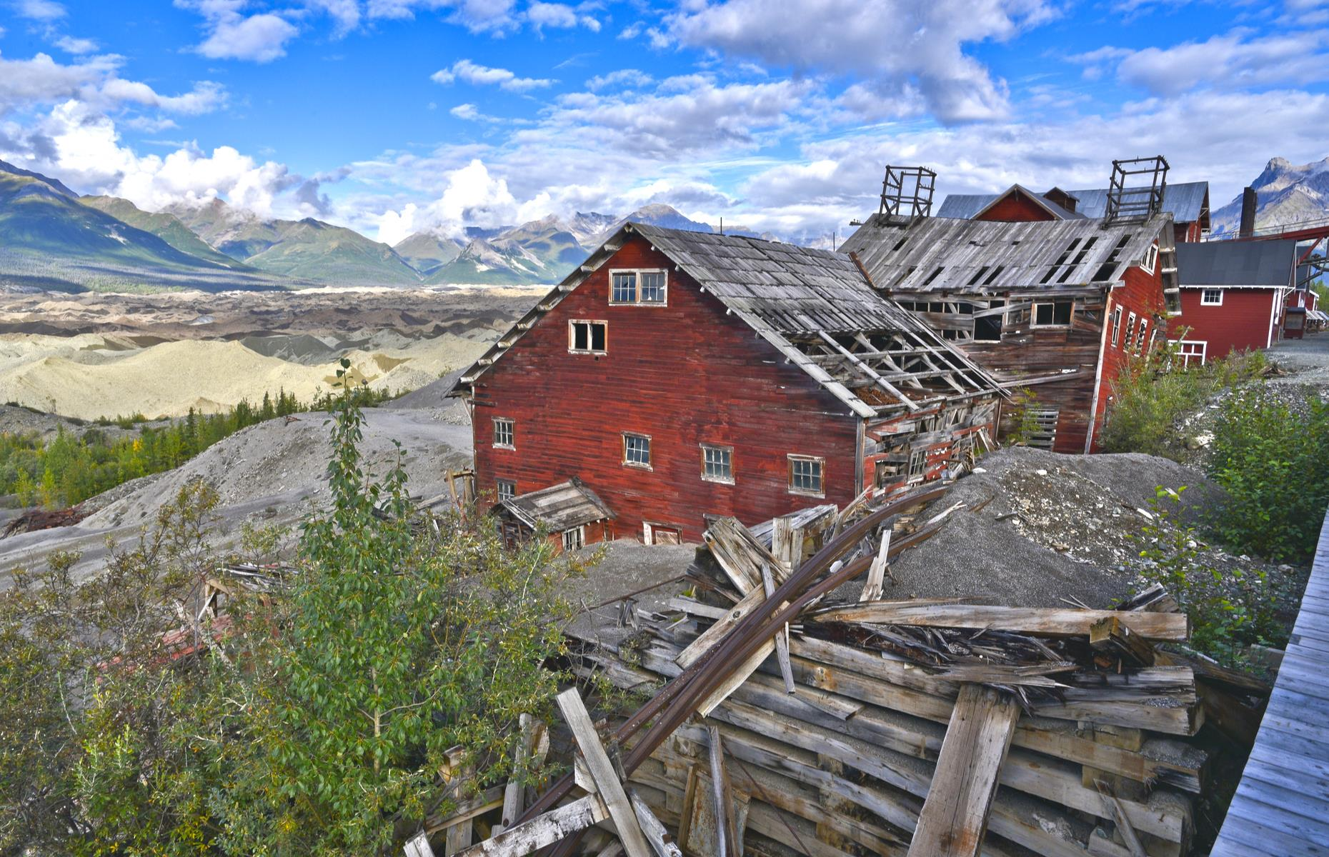 Slide 3 of 52: Protected today as a National Historic Landmark District, and within Wrangell-St Elias National Park, Kennecott (also Kennicott) was once a thriving copper-mining camp. But the site's existence was short-lived. Established in the early 1900s, the town was all but abandoned by 1938, as the area's copper reserves were exhausted, and the miners moved on. The site's deserted rust-red buildings and mountain views remain for visitors to explore, and interpretative rangers are currently available by phone.