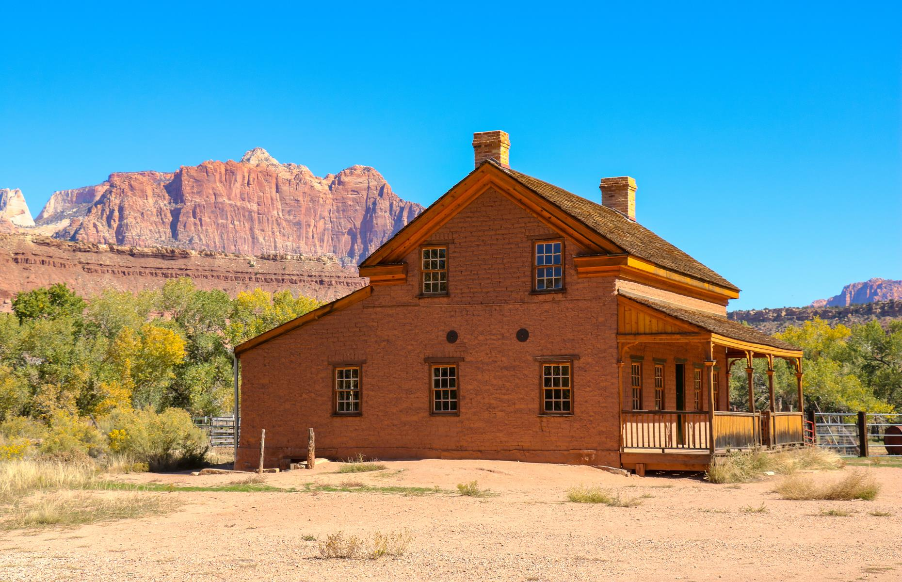 Slide 46 of 52: The rugged red peaks of Zion National Park watch over this ghost town. Once one of a large string of nearby villages, it was established by Mormon settlers from around 1859 – though the site we see today was built up in 1862 after a flood devastated the original town. It was inhabited until the early 1900s, when most residents moved west in search of a new life. The fascinating deserted homes, the atmospheric cemetery and the sheer natural beauty typically draw visitors to the site.