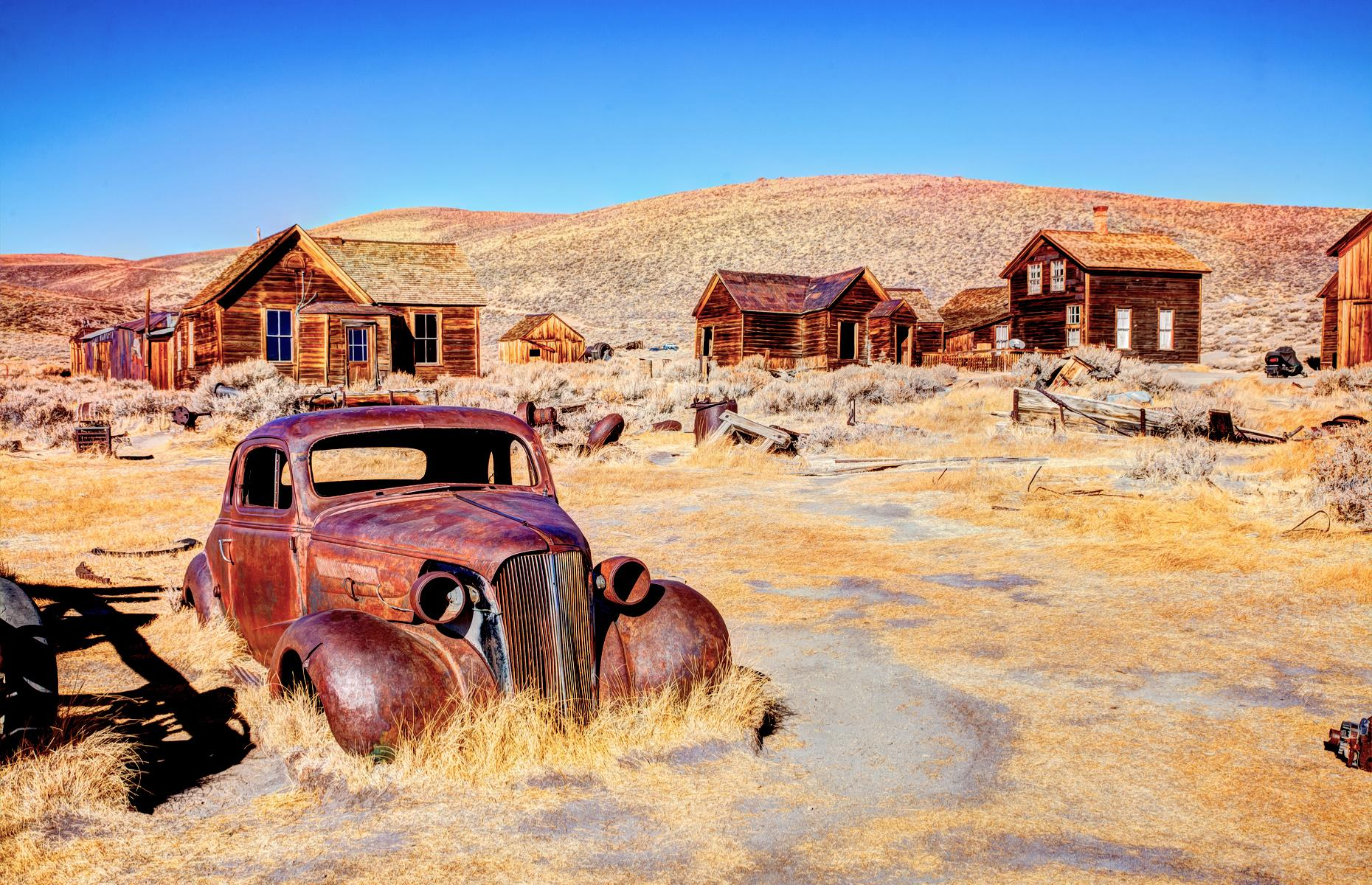 Slide 6 of 52: One of the best-known and most wonderfully preserved ghost towns in America, Bodie is tucked away in California's Eastern Sierra region. The town was at its peak between 1877 and 1882, when the mining industry was booming, and some 10,000 people called Bodie home. Now those residents are long gone, but around 200 ramshackle wooden buildings – including a saloon and a barber shop – give visitors a taste of the past. Entry to the historic buildings is currently suspended, but it's still possible to take a self-guided tour of Bodie's dusty, deserted streets.