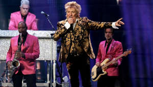 Rod Stewart standing on a stage: The rocker was held at gunpoint in 1982 whilst on the streets of LA. The thieves took the keys to his 1977 Porsche Turbo-Carrera, which was valued at $50,000 at the time. Stewart later lost his Dodge Viper in 2004 when a fired labourer working on his Florida mansion stole from him.