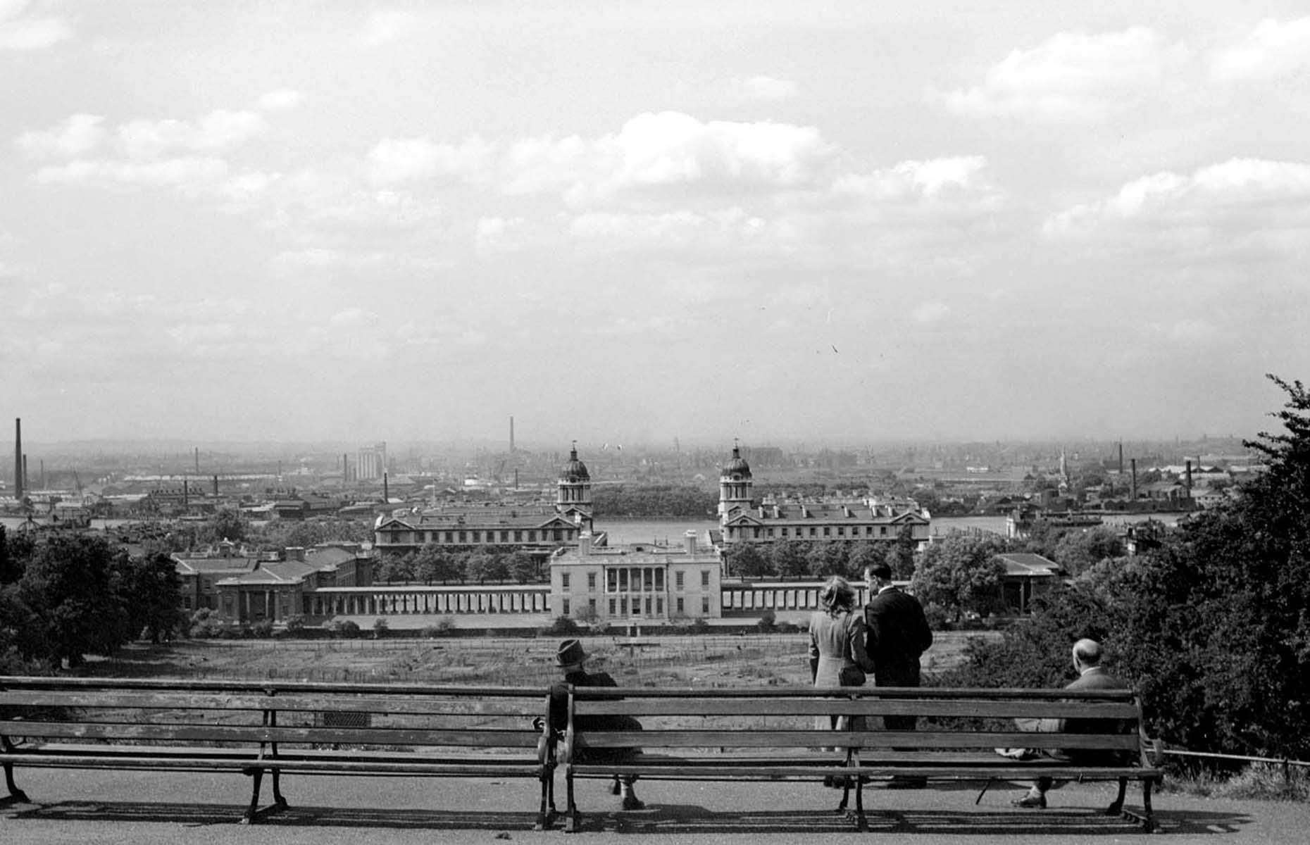 Slide 2 of 27: Captured from Greenwich Park sometime between 1945 and 1965, the Old Royal Naval College and Queen's House dominate the landscape here while, directly opposite, the view of the Thames' north bank is characterized by countless factory chimneys. Canary Wharf, alongside the Isle of Dogs, Limehouse and Poplar, were among the busiest docks in the world. After the 1960s, the port industry here declined and the docks closed completely by 1980.