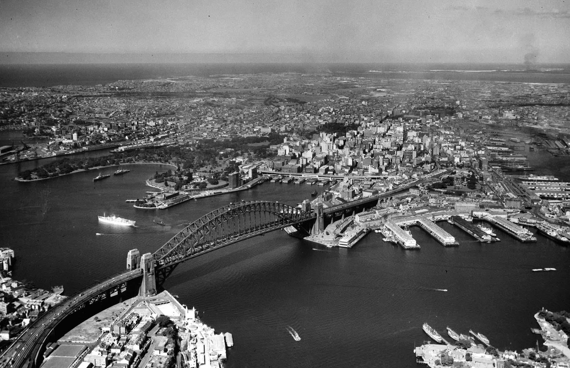 Slide 20 of 27: Australia's most populous city, Sydney has a tumultuous history, marred by countless conflicts, leading up to the 19th century when the situation stabilized and the city established itself as a major cultural and financial center in Australia. Although the Great Depression hit the country hard, the iconic Sydney Harbour Bridge was opened in May 1932. After the war, the city boomed and new industries grew, inspiring widespread development. But, captured here in 1955, Sydney Harbour is still missing a key landmark that was opened in 1973...