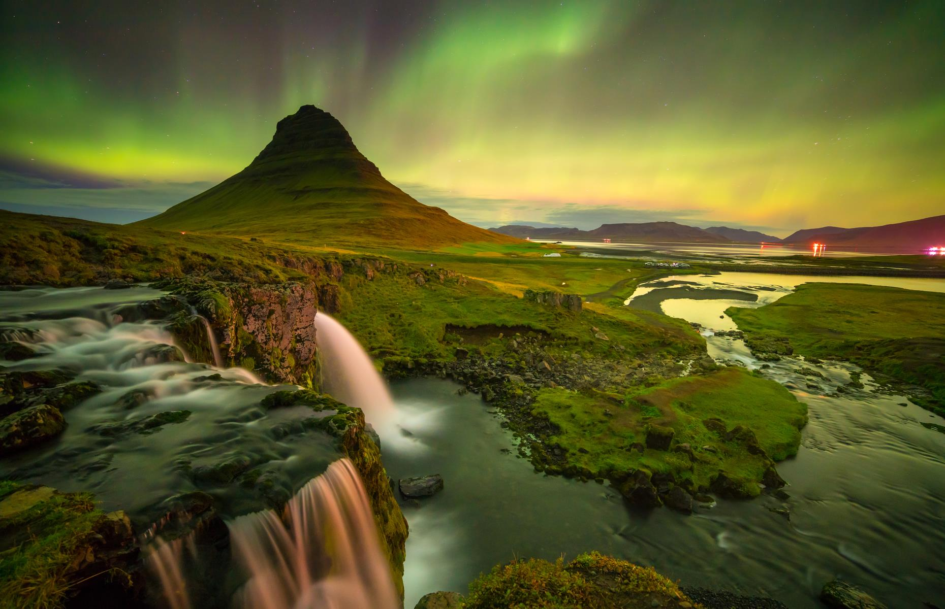 Slide 4 of 25: Located in the Snæfellsnes Peninsula near the town of Grundarfjörður, the pointed peak of Kirkjufell mountain is one of Iceland's most iconic inhabitants, measuring 1,519 feet high (463m). Within walking distance is another picture-perfect sight: Kirkjufellsfoss, which means 'Church Mountain Waterfalls'. The area's natural beauty is only enhanced by the aurora borealis (another name for the Northern Lights), sometimes referred to as the 'merry dancers'.