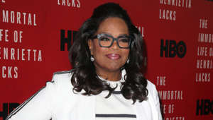 Oprah Winfrey holding a sign: The Queen of talk shows took her reign in 1986 as he first black woman to host a national talk show in America.  Oprah would later become the first black woman to own and produce her own show.  Since finding fame in the 80s, she went on to become the first black multi-billionaire with an estimated net worth of $2.5 billion.