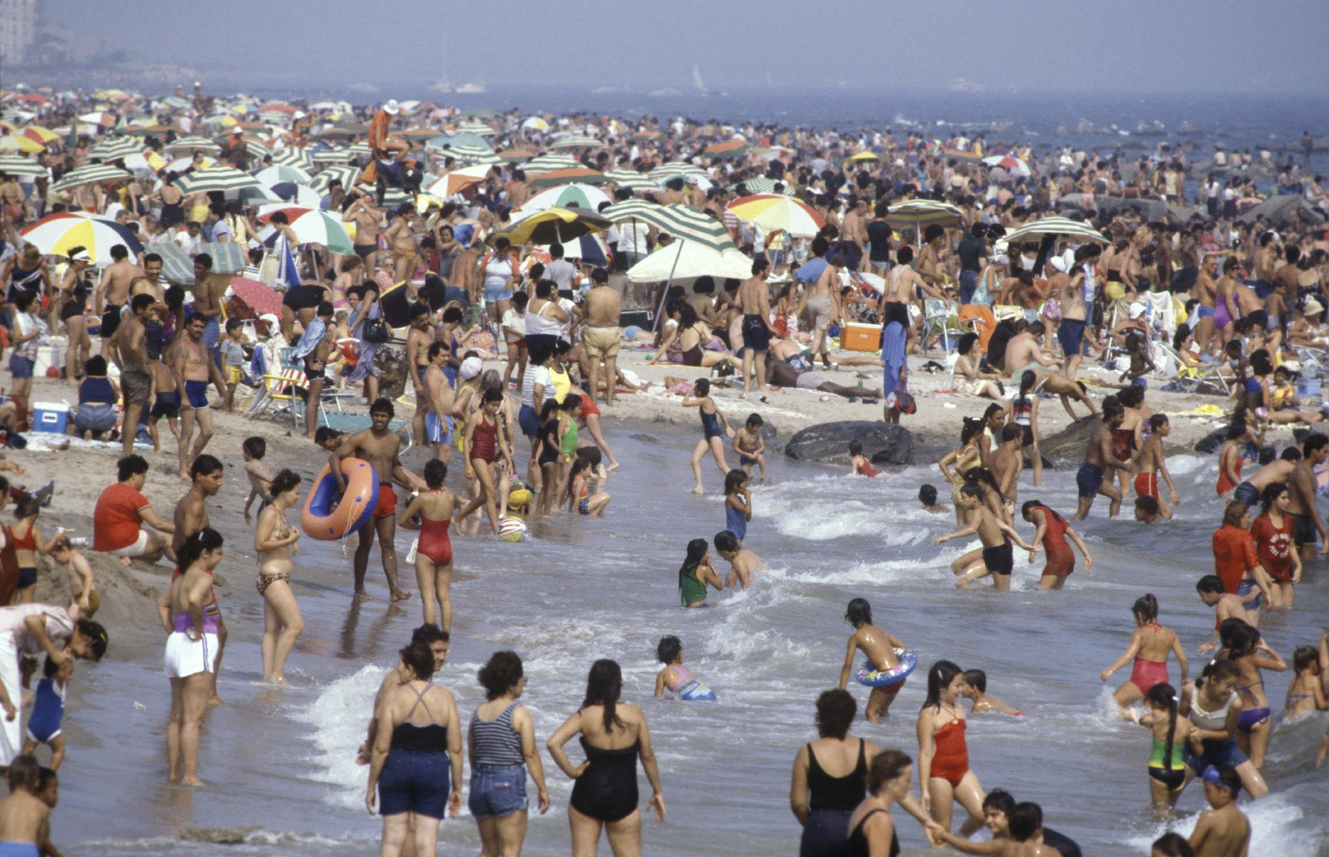 Slide 29 of 38: Back on American soil, the shores were busier than ever too. Here, at the tail end of the decade, Coney Island's sandy strand swarms with people. Rubber rings, umbrellas, beach towels and balls add splashes of color to Brooklyn's humming beach, as families enjoy their vacation time.