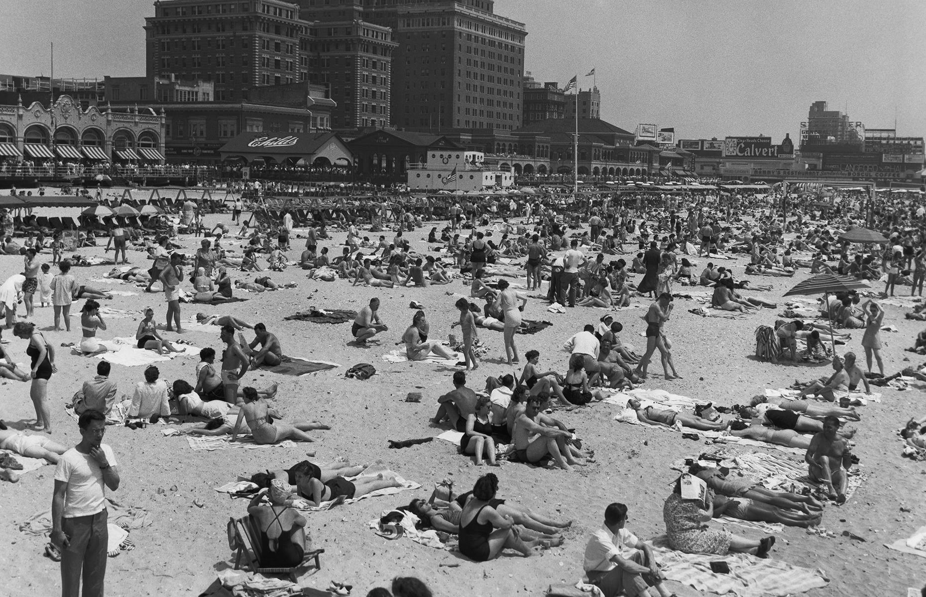 Slide 3 of 38: In the post-war years, beachside destinations on America's East Coast boomed. Here families, friends and couples relax on Atlantic City's sandy beach, while the hotel-lined boardwalk thrums behind them.