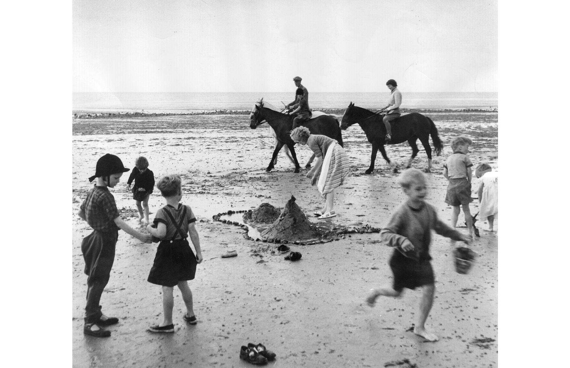 Slide 15 of 38: The seaside escape remained the ultimate British vacation through the 1950s –think ice cream and fish and chips, pony rides and puppet shows, and the windswept shores of the English coast. In this 1954 photo, families play on the sand in Angmering in West Sussex.