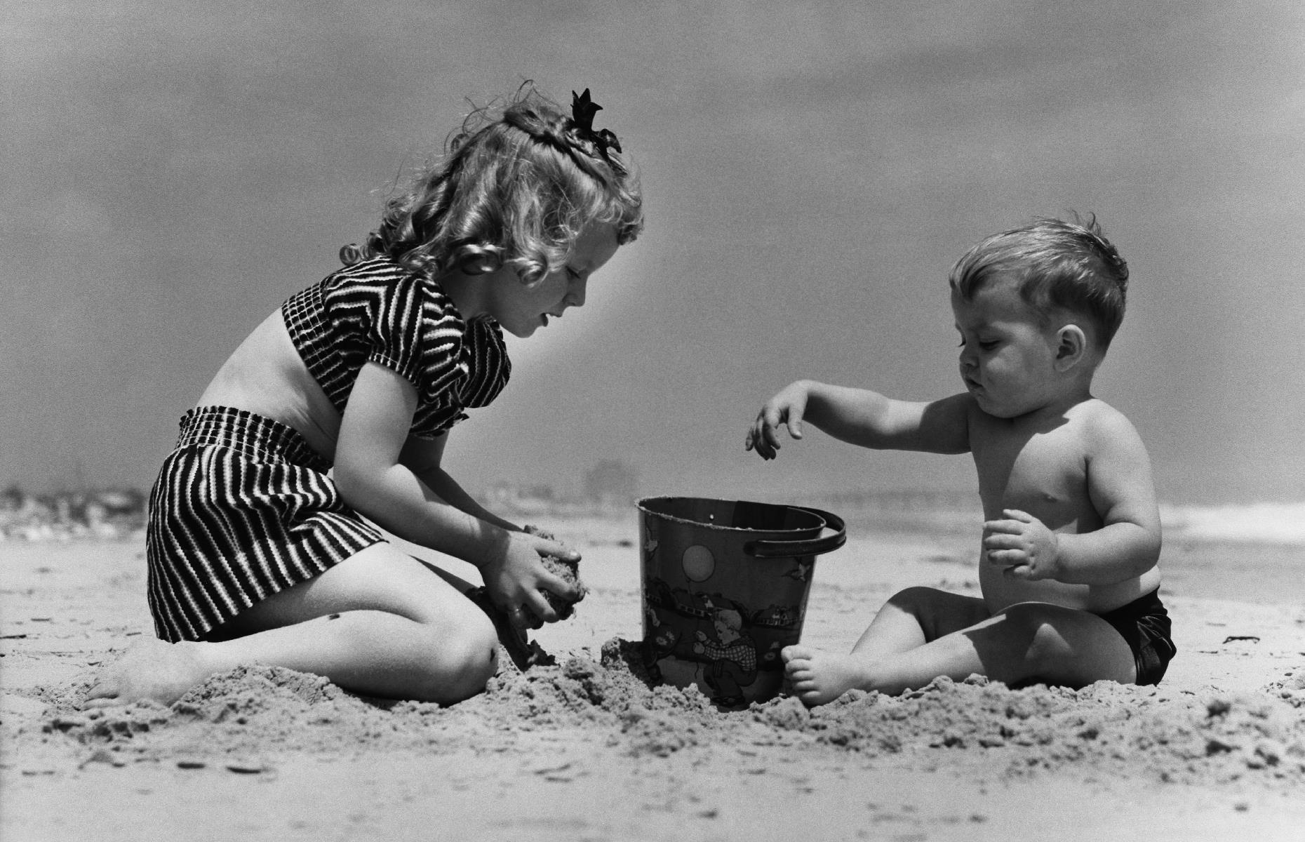 Slide 5 of 38: Not all destinations had as many bells and whistles, though. Where there weren't rides, puppet shows and cotton candy stands, little beach-goers would make do with a bucket and spade. Here a young brother and sister build a sandcastle on a beach in Florida.