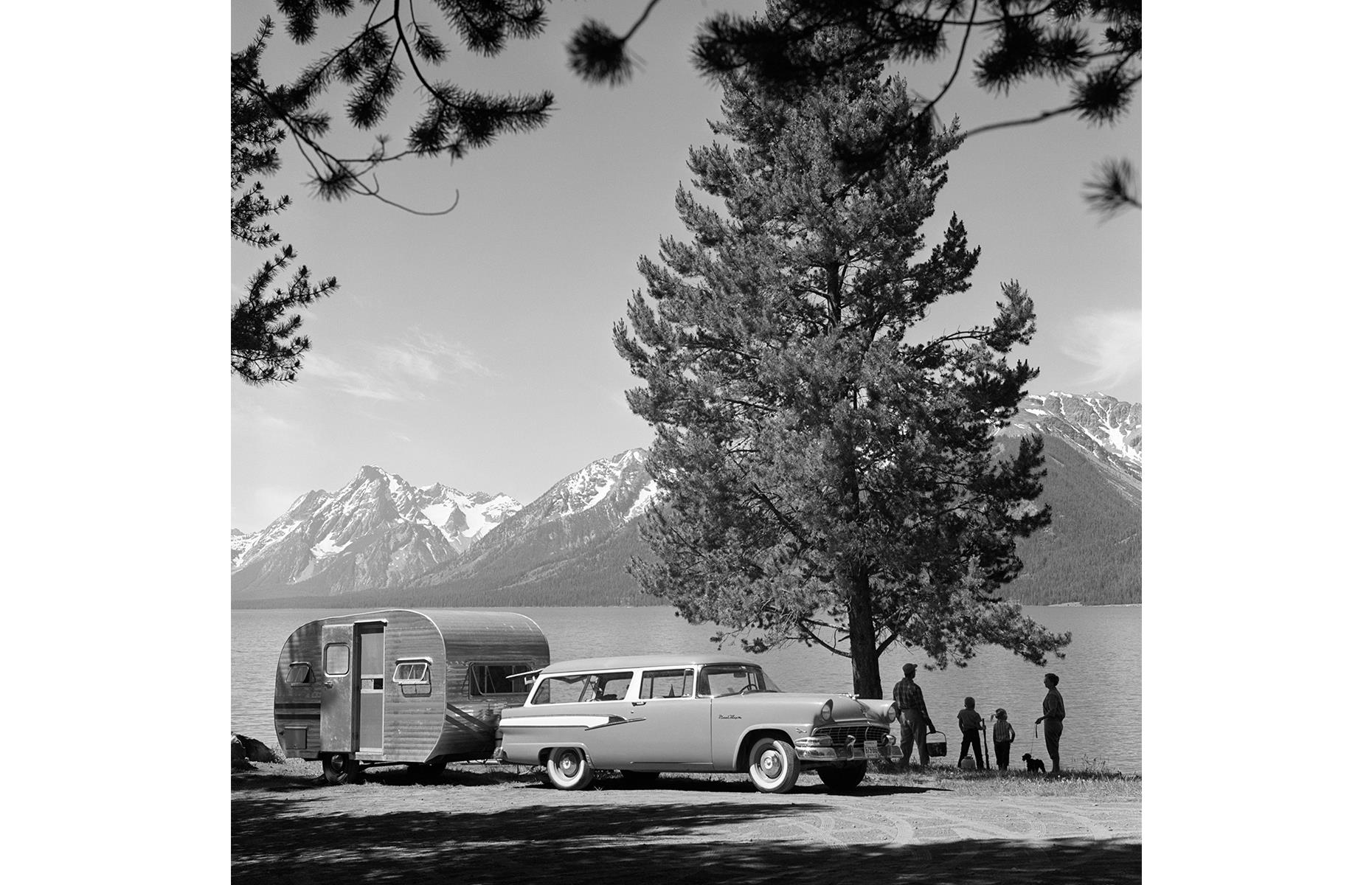 Slide 9 of 38: While some families made a beeline for the coast, others decided to enjoy America's backyard with their cars, trailers and motorhomes. Here the Tetons rise above Jackson Lake in the Grand Teton National Park, established in 1929. A young family look out at the view, picnic in hand, trailer parked up at the water's edge.