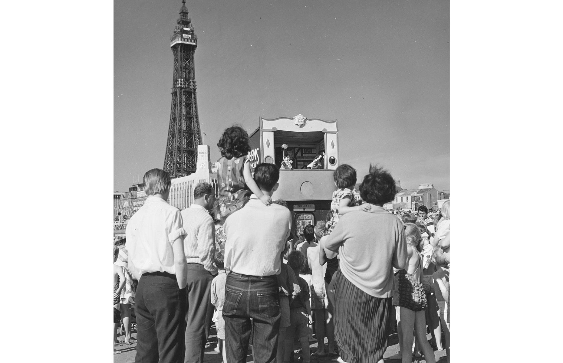 Slide 20 of 38: The northwest of England laid claim to one of Britain's most popular holiday spots in the 1960s. In summer, Blackpool Beach, with its piers and promenade, would play host to throngs of holidaymakers, who rode donkeys, ate ice cream and lazed on the sands. It's still a popular spot today, and in this heartwarming 1960s shot Blackpool Tower is the backdrop for a family puppet show.