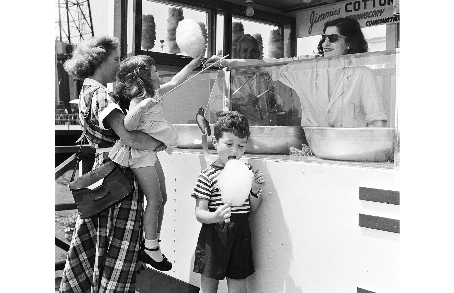 Slide 4 of 38: Farther up the coast, Coney Island – with its theme parks, sandy beach and family-friendly amusements – was another place that thrived towards the end of the decade. Cotton candy is the snack of choice here and, in this nostalgic shot, a child gladly takes a sweet candy cloud from a smiling vendor.