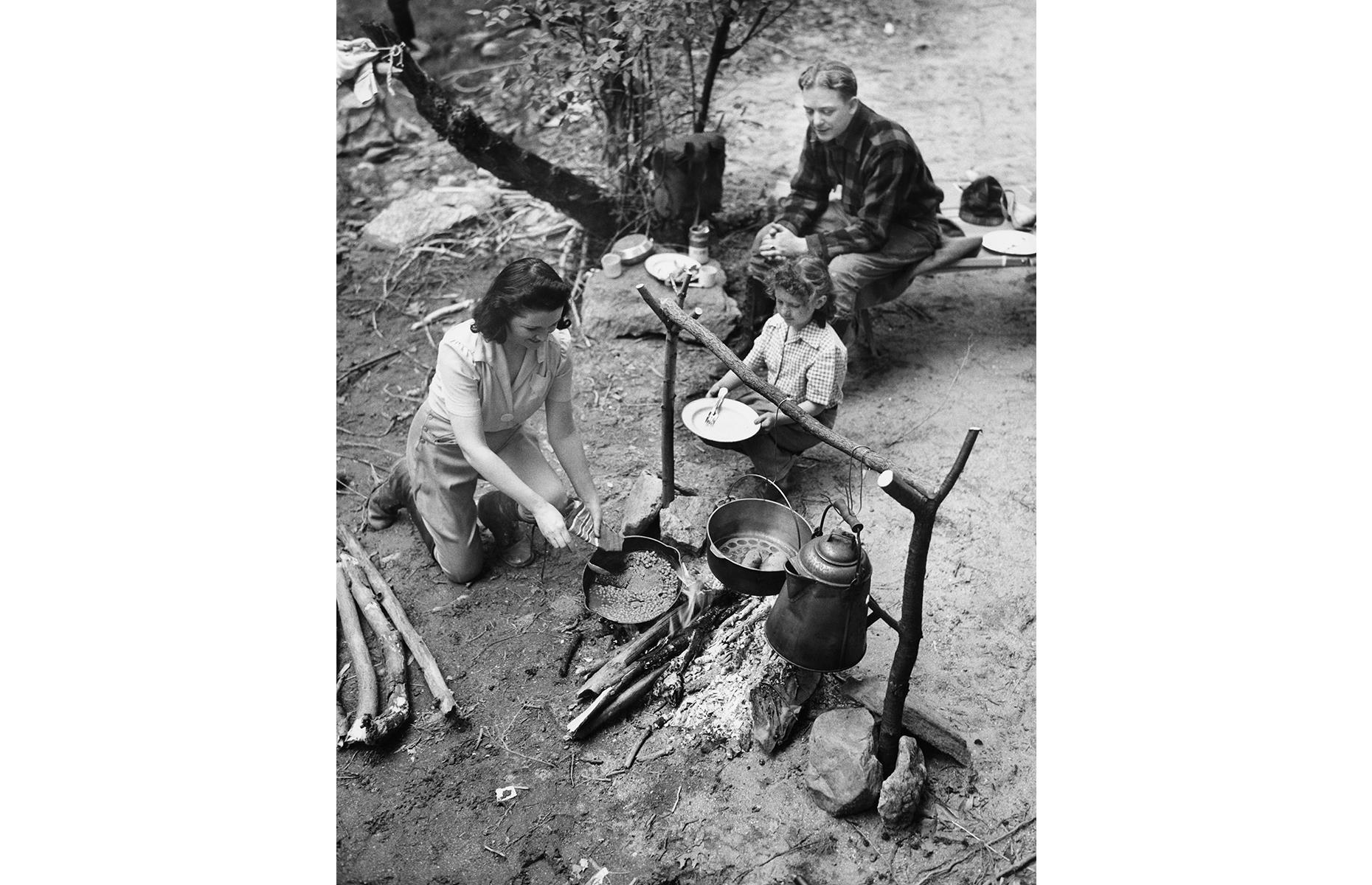 Slide 2 of 38: This was a decade shaped by the Second World War and, even post-war, most families spent their holiday time close to home. Trailer parks and campsites were top places to escape, with destinations such as the Adirondacks, in New York, proving popular with outdoorsy types. Here a mother serves dinner cooked over a campfire to her family, perhaps after a long day of hiking.