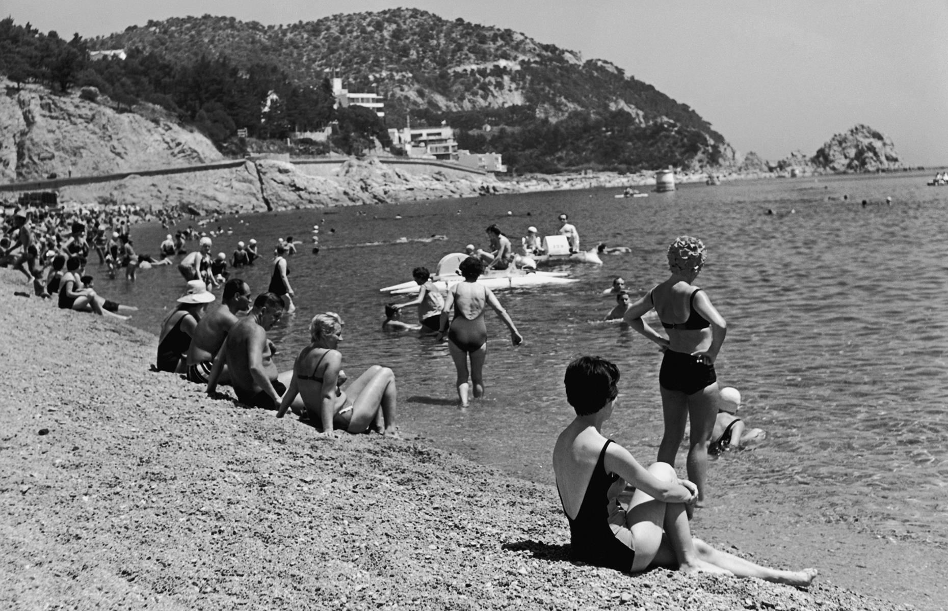 Slide 16 of 38: By the 1960s, Spanish seaside resorts such as Benidorm in Costa Blanca buzzed with people, attracting tourists from Britain and beyond. Package holidays grew in popularity during this decade too. In this Sixtiessnap, holidaymakers bask on a beach in Tossa de Mar, Costa Brava in northeastern Spain.