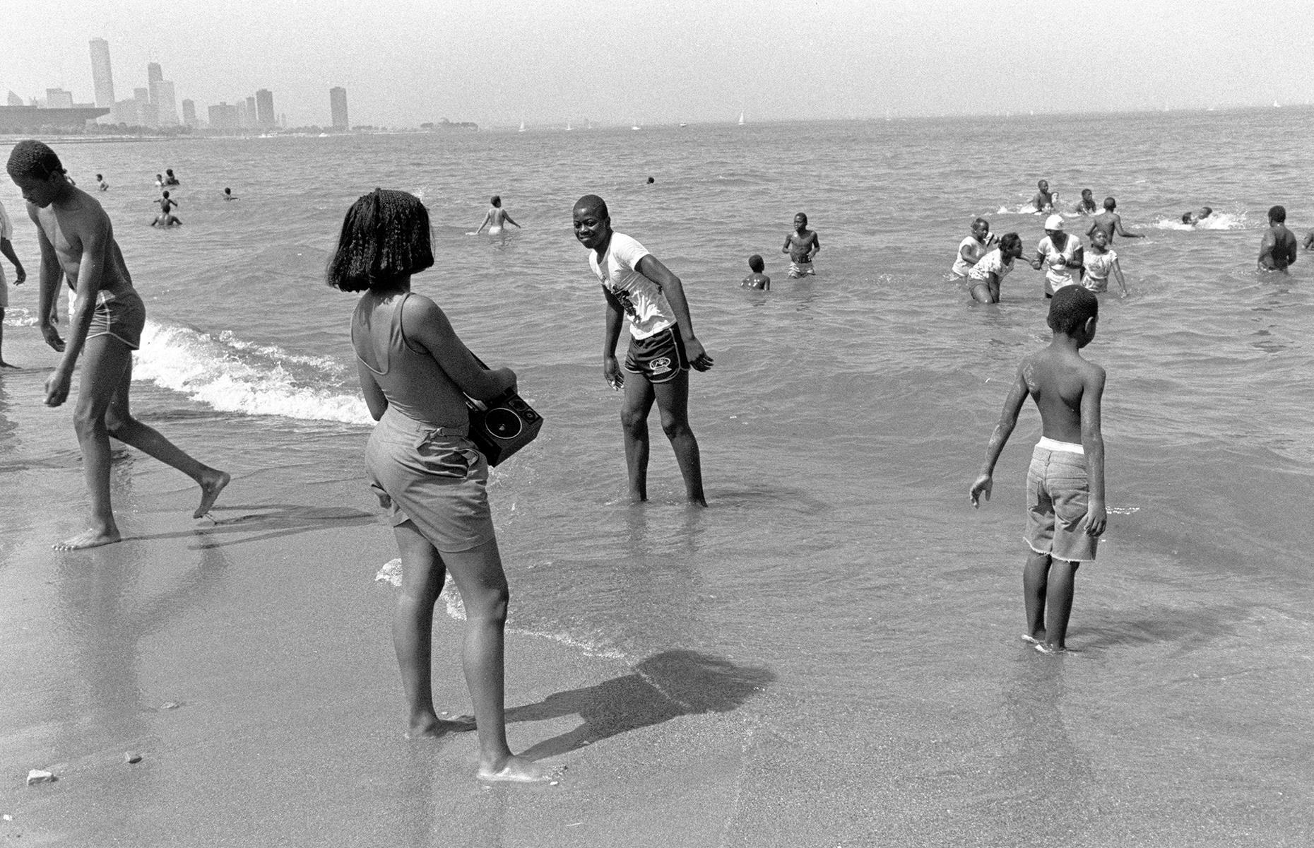 """Slide 30 of 38: It's not all about the seaside, though – America's Great Lakes have long been a vacation spot for beach bums too. In this 1987 snap, sun seekers splash in Lake Michigan at Chicago's Margaret T. Burroughs Beach (formerly 31st Beach). Now a diverse city strand, this beach was once segregated and designated for black visitors. And in contrast to the peaceful scenes shown here, a black teenager named Eugene Williams was killed in these waters, when he unknowingly drifted into a """"white zone"""", triggering the Chicago race riot of 1919. A memorial for Williams is held on the beach each year."""