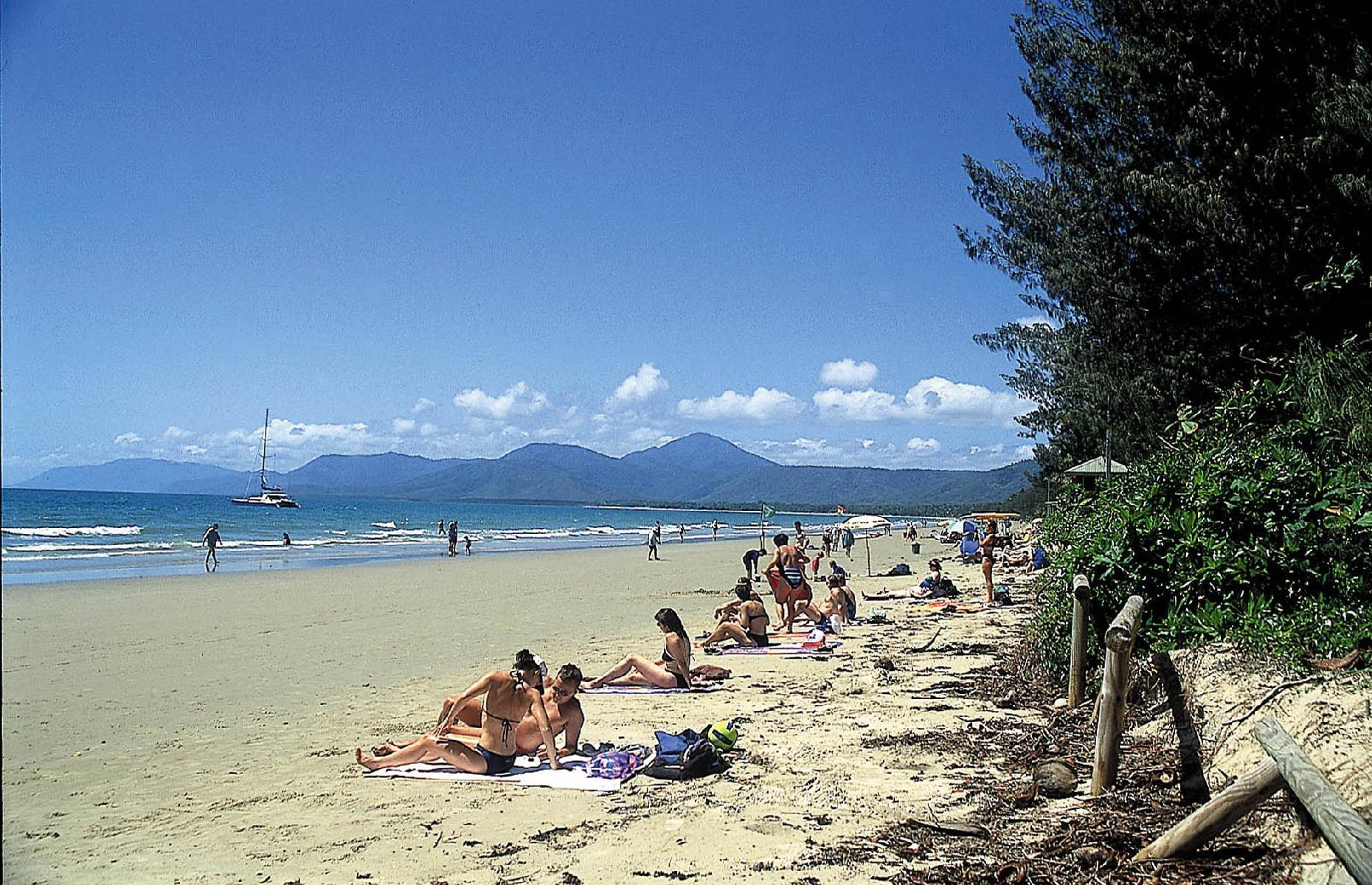 Slide 37 of 38: The world continued to shrink in this decade too, with families who were wealthy enough making bucket-list-style trips and exploring all corners of the globe. Here families and couples sunbathe on Four Mile Beach in Port Douglas, Queensland, a jumping-off point for the Great Barrier Reef. Inspired? Check out these incredible places you won't believe are in Australia.