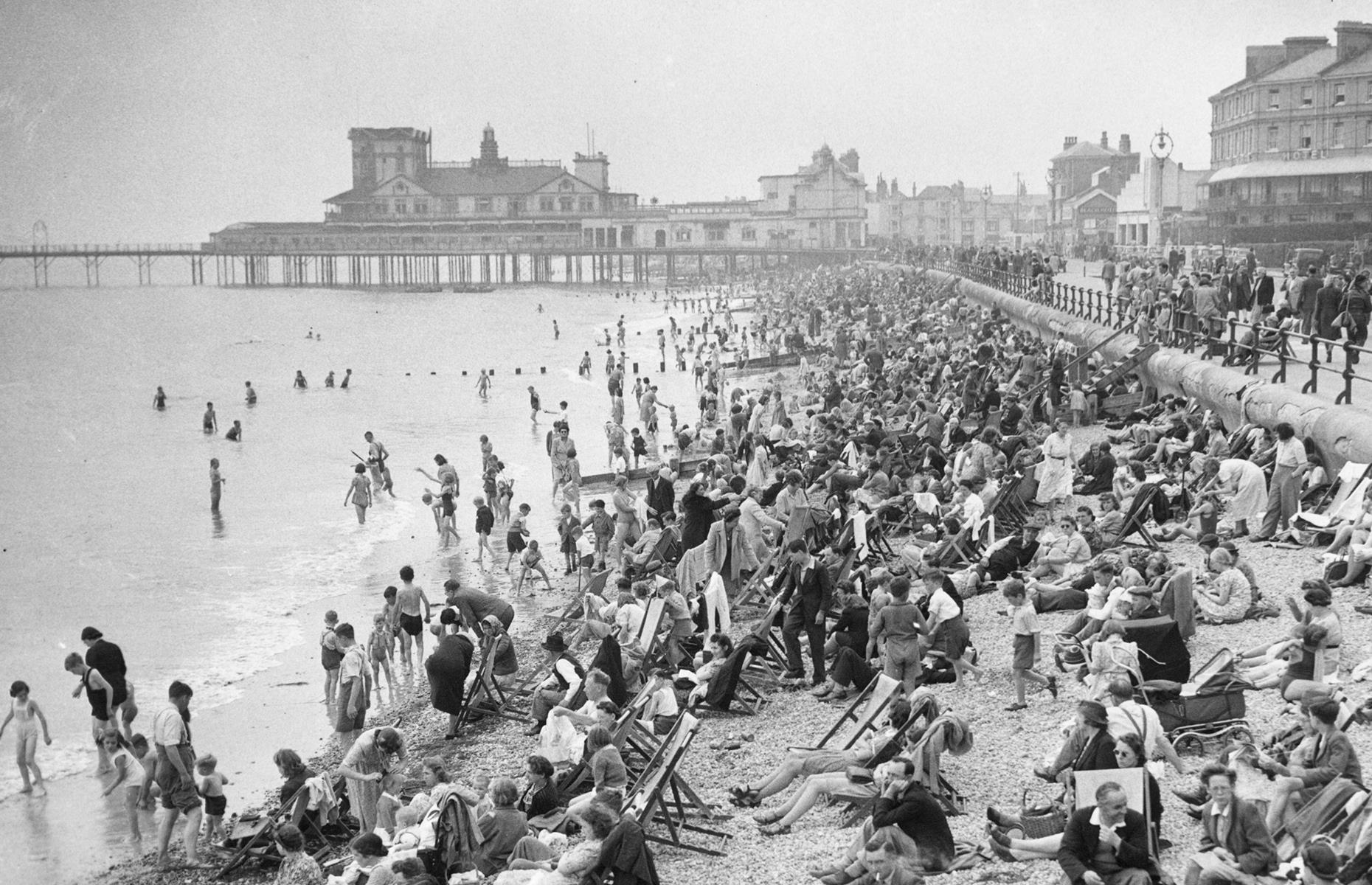 Slide 7 of 38: As the war drew to a close, resort towns such as England's Bognor Regis were flourishing once more. You can barely see the shingle for sunbathers in this photograph taken in 1945. The promenade lining the beach hums with people too.