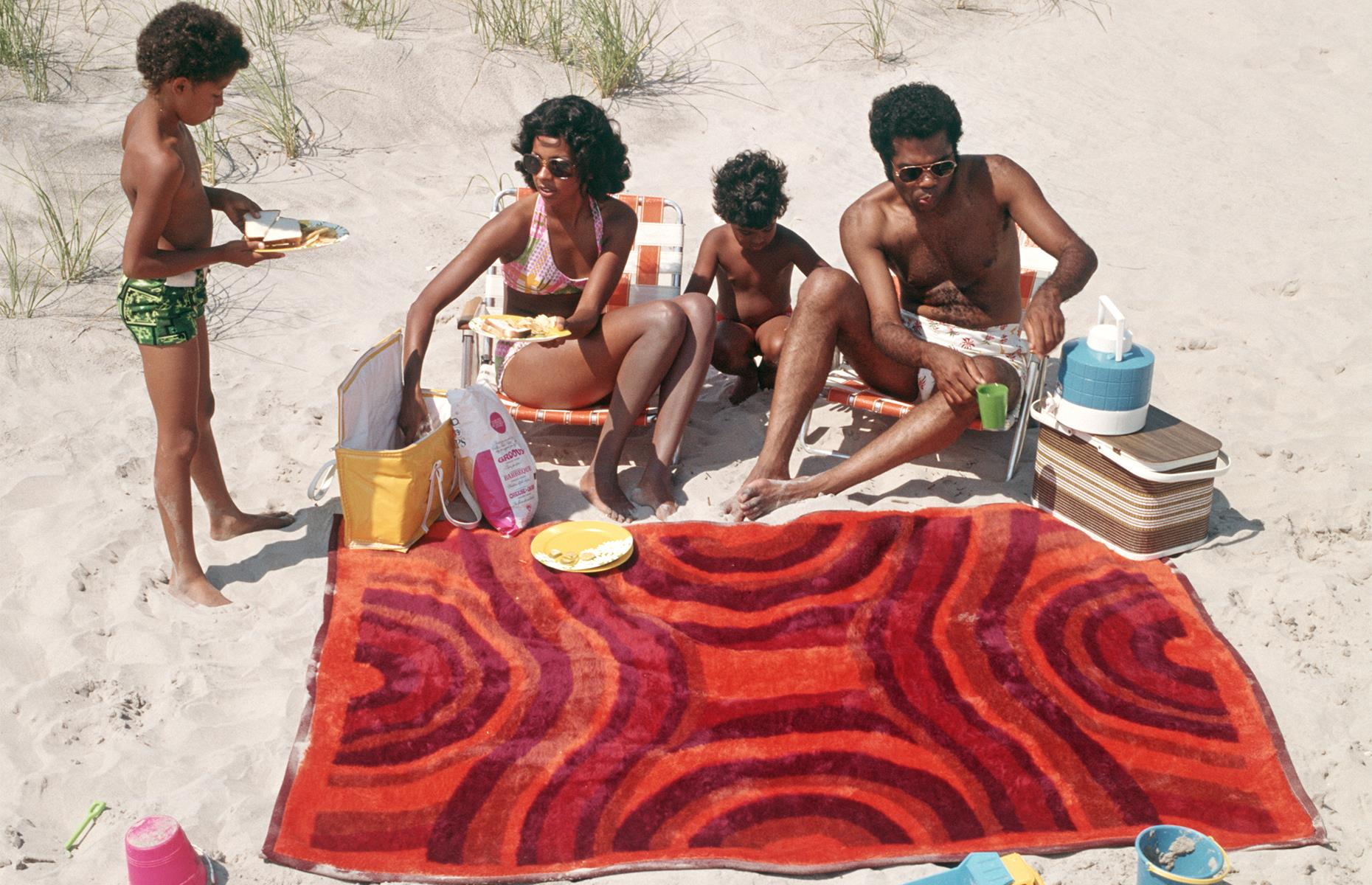 Slide 25 of 38: But despite the theme parks, the cruise ships and the call of the Continent, many Americans still vacationed closer to home. Here a young family picnic on a quiet beach on a sun-drenched afternoon in New Jersey.